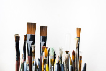 Various colorful used brushes for art on white background
