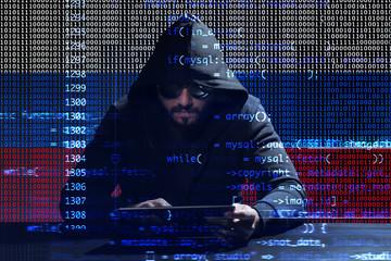 Hacker using tablet on dark background