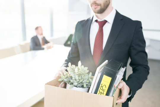 Mid section portrait of handsome businessman holding box of personal belongings  leaving office after quitting job, copy space