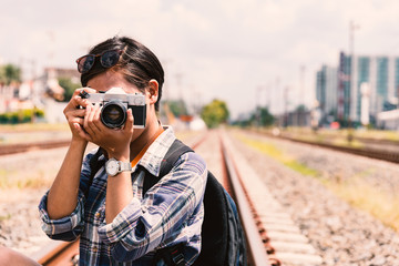 young hipster Asian woman wearing plaid shirt holding the camera vintage