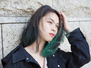 Beautiful young girl with green hair posing outdoor. Sunny portrait of glamour Chinese stylish lady. Emotions, people, beauty and lifestyle concept.