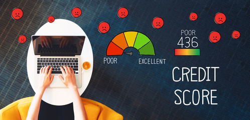 Poor Credit Score with person using a laptop on a white table