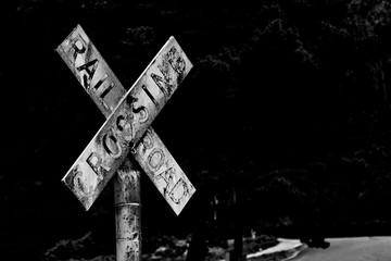 Old vintage retro distressed railroad crossing sign with worn faded text