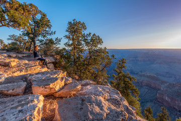Girl is Seating on the Edge of Grand Canyon and Meeting Sunrise in the Firs Rays