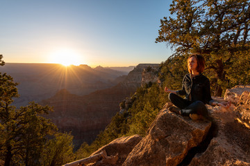 Girl is Seating and Doing Yoga on the Edge of Grand Canyon on Sunrise