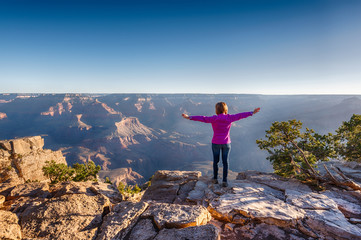 Girl in Purple Hoodie is Standing on the Edge of Grand Canyon