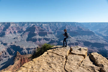 Tourist Girl in Jeans Suite is Standing on the Edge of Grand Canyon and Photographing