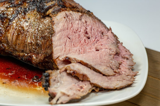 Grilled tri tip steak sliced on a white plate on the kitchen table