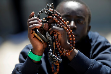 A migrant holds mobile phones and pendants as he rests after arriving on a rescue boat at the port of Tarifa
