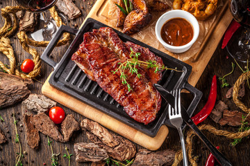 Arabian cuisine in Dubai. A roasted beef steak, with sauce, on a wooden board. The concept is a beautiful serve in the restaurant. Background image. Copy space, selective focus