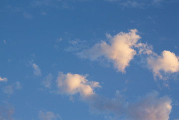 Blue sky with fluffy golden clouds at twilight.  Background and textures.