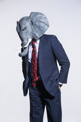 A man in a suit and an elephant mask on a light background. Conceptual business background