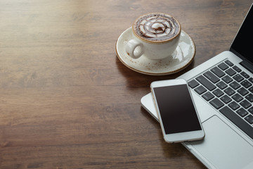 Laptop computer and mobile phone, hot coffee in white cup on wooden table with sunlight and copy space.