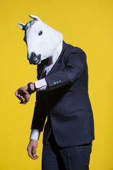 A man in a suit and a horse mask looking at his watch. Yellow background. Conceptual business background