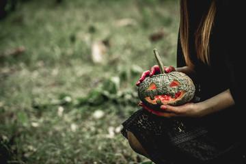 Girld dress black as angel of death and holding demon pumpkin and kira angkor in Halloween festival. Halloween concept. Psychopomps.