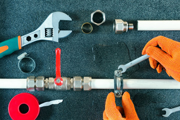 Plumbing concept. tools and pipes on a dark slate background.Hands plumber repairing water pipe.