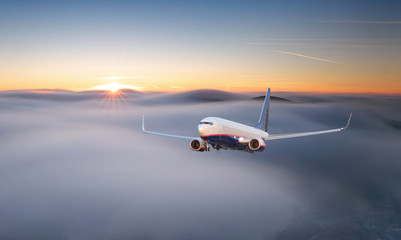 Passenger airplane. Landscape with big white airplane is flying in the red sky over the clouds and sea at colorful sunset. Passenger aircraft is landing at dusk. Business trip. Commercial plane.