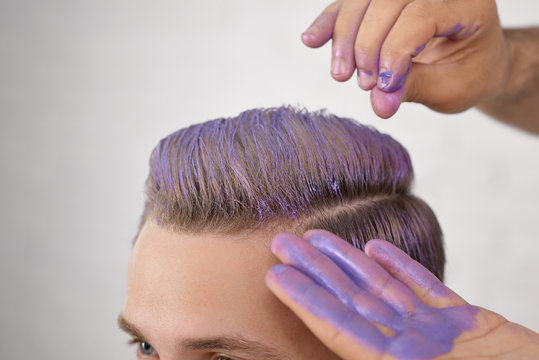Barber's hand toning young client's hair in violer color. Hands are washed out with spots of violet paint. Working on white studio background. Model looking forward, having blue eyes.