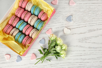 Box with tasty macarons and roses on light background, top view