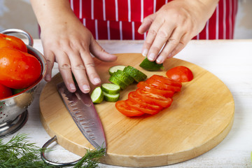 Woman is cutting vegetables for a salad