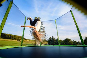 Kind auf Trampolin - Salto rückwärts dynamisch