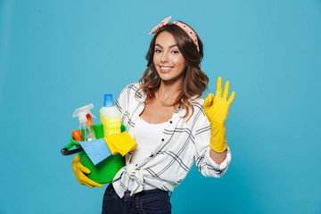 Photo of caucasian pretty housemaid 20s wearing yellow rubber gloves for hands protection holding bucket with cleaning supplies, isolated over blue background Wall mural