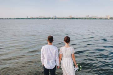 Beautiful newlyweds standing with their backs against the sea and holding hands. Stylish bride and groom. Wedding portrait.