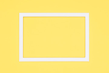 Abstract flat lay pastel yellow colored paper texture minimalism background. Minimal template with empty picture frame mock up.