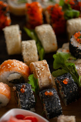 Sushi set food photo. Rolls served on brown wooden and slate plate. Close up of sushi