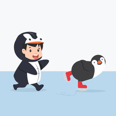 little kid characters in penguin costume with penguin  doing ice skating