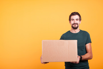 Attractive happy smiling delivery man with a cartboard box in his hands on yellow background in studio