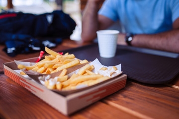 Selective focus paper tray with fried potatoes on a wooden desk in a restaurant with blurred man in the background