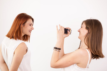 Two female friends playing with an action camera in studio over a white wall