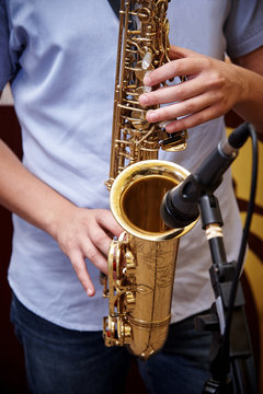 Saxophone in the hands of a musician.