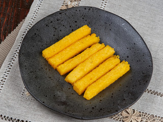 Fried polenta fingers set on a dark brown plate. A Romanian speciality.