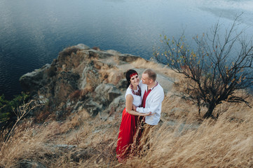 A couple in Ukrainian national clothes gently embrace near the river. Ukrainian wedding in old traditions.