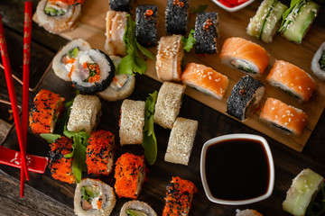 Sushi set food photo. Rolls served on brown wooden and slate plate. Close up and top view of sushi