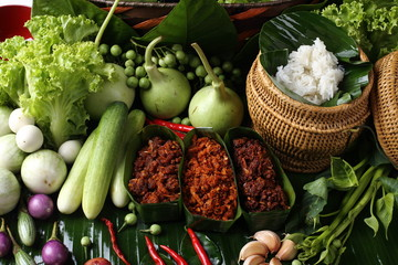 Famous Thai Food Hot and Spicy sauce with local ingredient fresh herb, paste sauce and vegetable arrange set , South East Asia style healthy food low price Top view on banana leaf