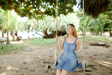 Young caucasian girl riding on swing and wearing jeans sundress, sand in background. Concept of summer vacations and leisure time.