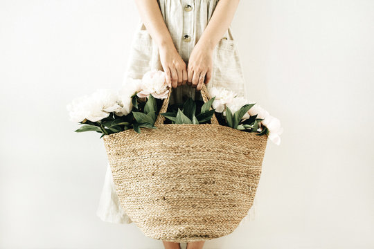 Young woman holding straw bag with white peony flowers on white background. Beauty concept.
