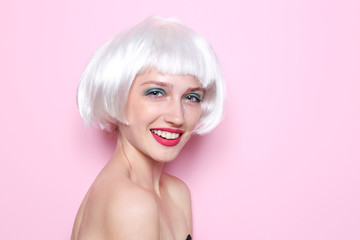 Young woman with wig and professional makeup on color background