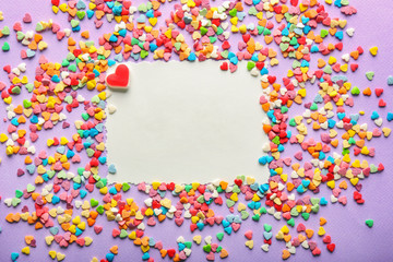 Blank card and different heart-shaped candies on color background