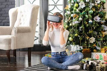 girl wearing virtual reality glasses first time, marketer get useful New Year present from parents. Lady with ponytail sitting near decorated pinetree unpacking gifts. Concept of innovative