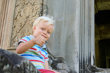 Cute little boy 4 years old blond hair sitting outdoor
