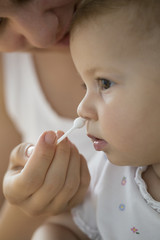 mother cleaning babies nose with cotton swabs