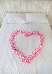 Heart of red petals on a bed. Honeymoon.