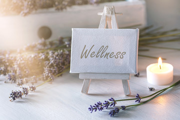 Spa or wellness still life: little image with lot of lavender in front of vintage wooden furniture and candlelight