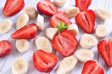 Fototapeta Ripe sliced strawberries and bananas on light wooden background obraz