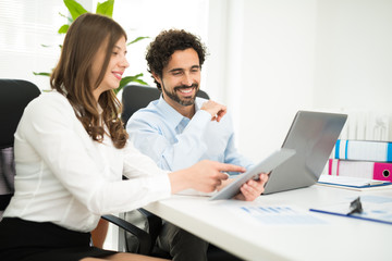 Smiling business people using a laptop computer