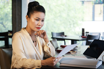 Side view of gorgeous Asian businesswoman in elegant light blouse reading attentively important documents sitting at cafe table with laptop on blurred backlit background